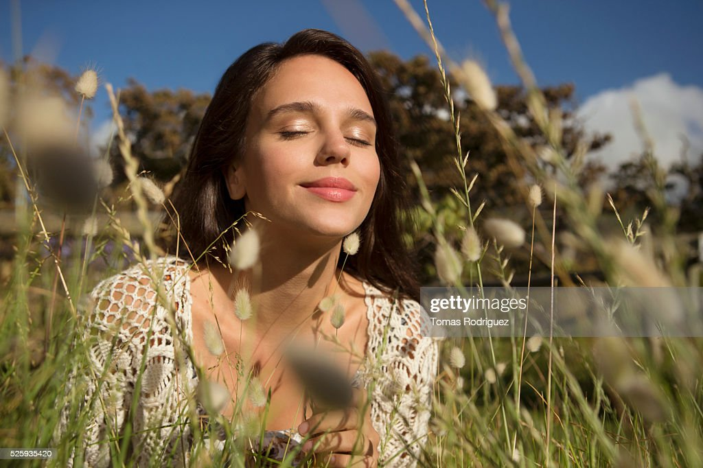 Young woman in grass with eyes closed : Stock Photo