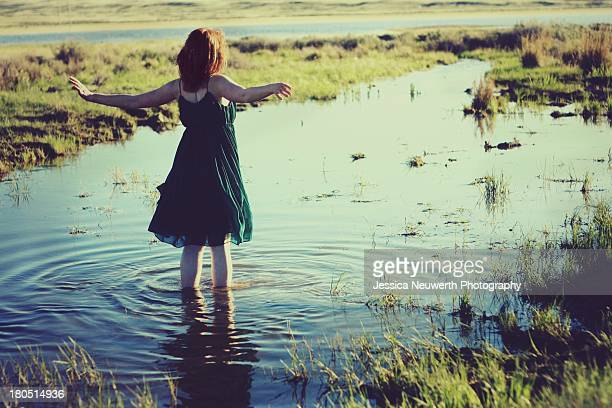 young woman in green dress standing in marsh - green dress stock pictures, royalty-free photos & images