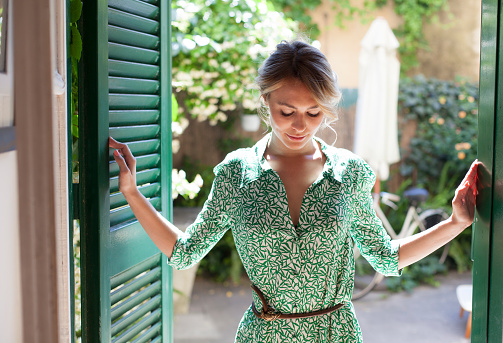 Young woman in green dress stepping inside from the garden - gettyimageskorea