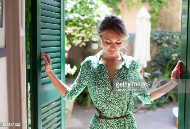 young woman in green dress stepping inside from the garden - kleid stock-fotos und bilder