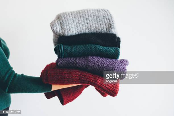 young woman in green sweater stand on the side holding stack of five different knitted warm winter sweaters - abiti pesanti foto e immagini stock