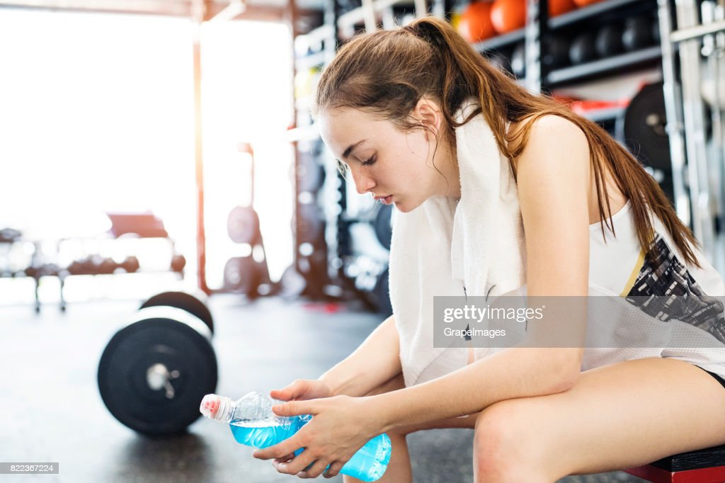Young woman in gym after finishing work out, white towel around her neck, holding water bottle. : Stock Photo