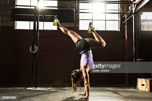 Young woman in gym doing handstand