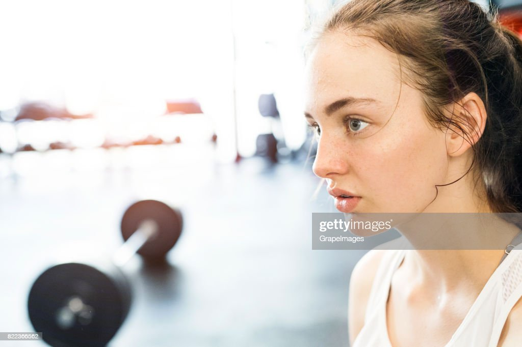 Young woman in gym, in white tank top, resting, heavy barbell next to her. : Stock Photo