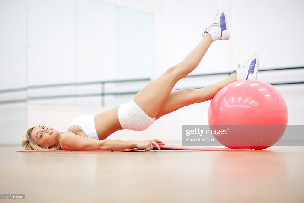 Young woman in gym training with exercise ball : Stock Photo