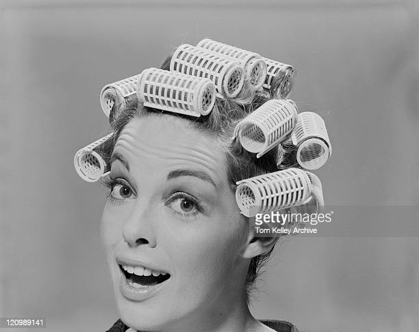 young woman in hair rollers, portrait - krulspelden stockfoto's en -beelden