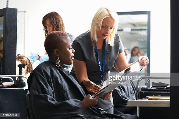 Young woman in hair salon wearing hair cutting cape choosing hair dye colour from swatches