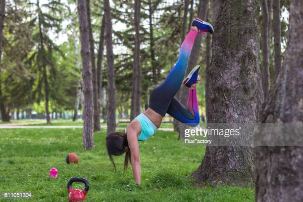 young woman in handstand pose - circuit training stock photos and pictures