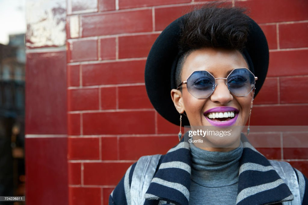 Young woman in hat and sunglasses against a wall, horizontal : Stock Photo