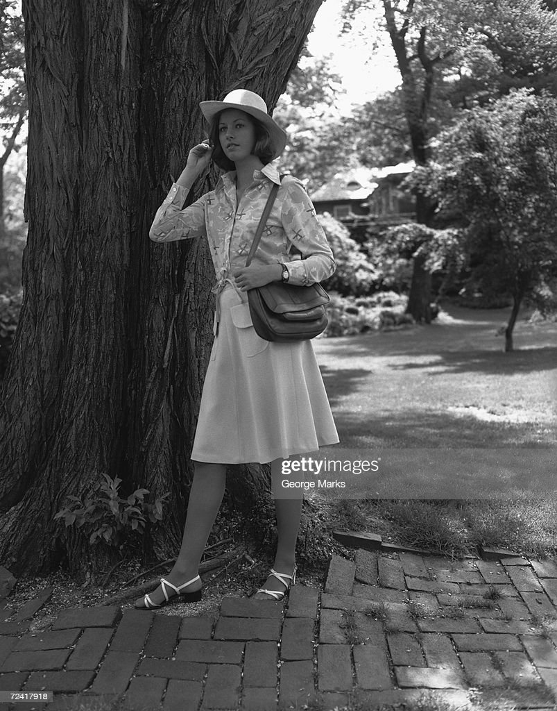 Young woman in hat standing by tree, (B&W), : Stock Photo