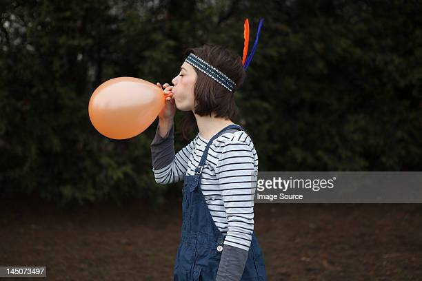 Young woman in headdress, blowing up a balloon