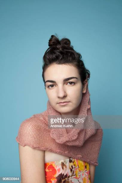Young woman in her late teens in front of a blue background wearing a colorful top and a neck wrap scarf, portrait.