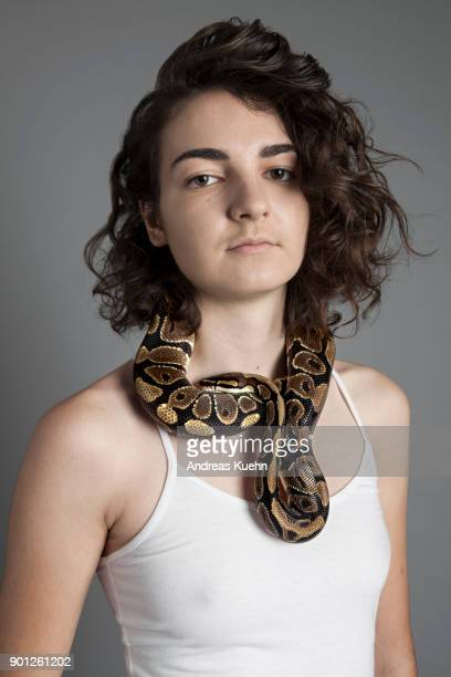 Young woman in her late teens wearing a white tank top in front of a gray background with a ball python around her neck, portrait.
