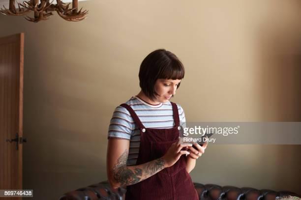 young woman in her living room texting - bordeauxrood stockfoto's en -beelden