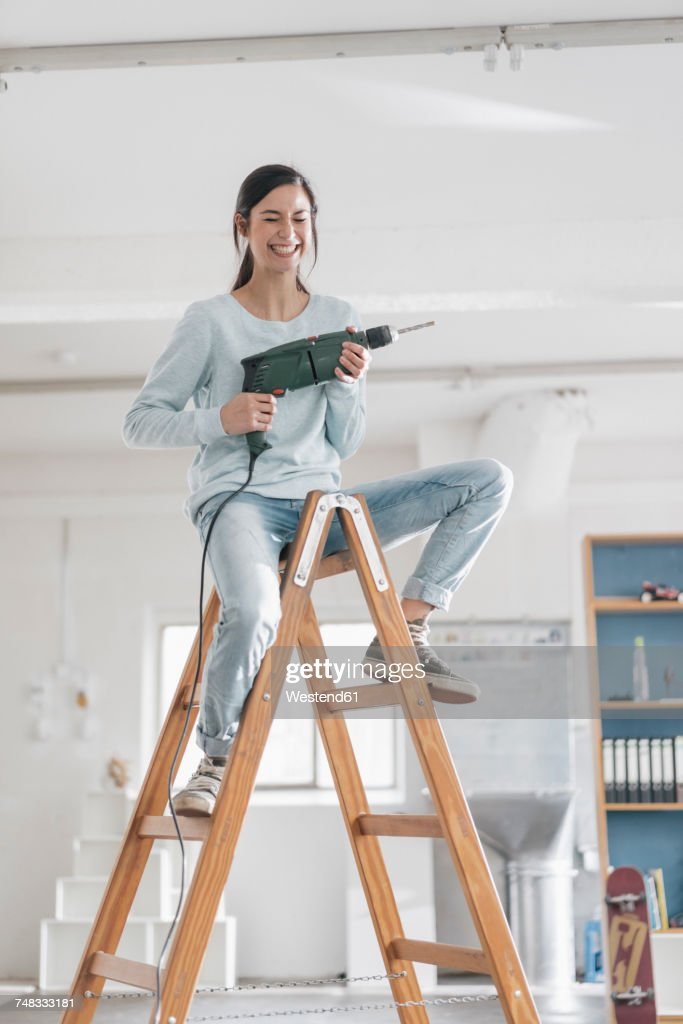 Young woman in her new flat sitting on ladder, holding electric drill : Stock Photo