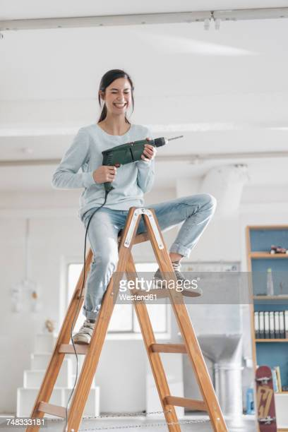 young woman in her new flat sitting on ladder, holding electric drill - taladro fotografías e imágenes de stock