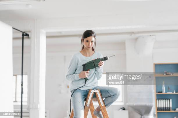 young woman in her new flat sitting on ladder, holding electric drill - unabhängigkeit stock-fotos und bilder