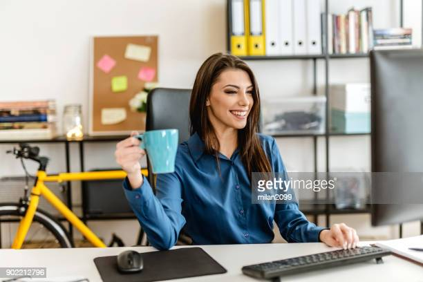 young woman in her office, working and drinking coffee - milan2099 stock photos and pictures