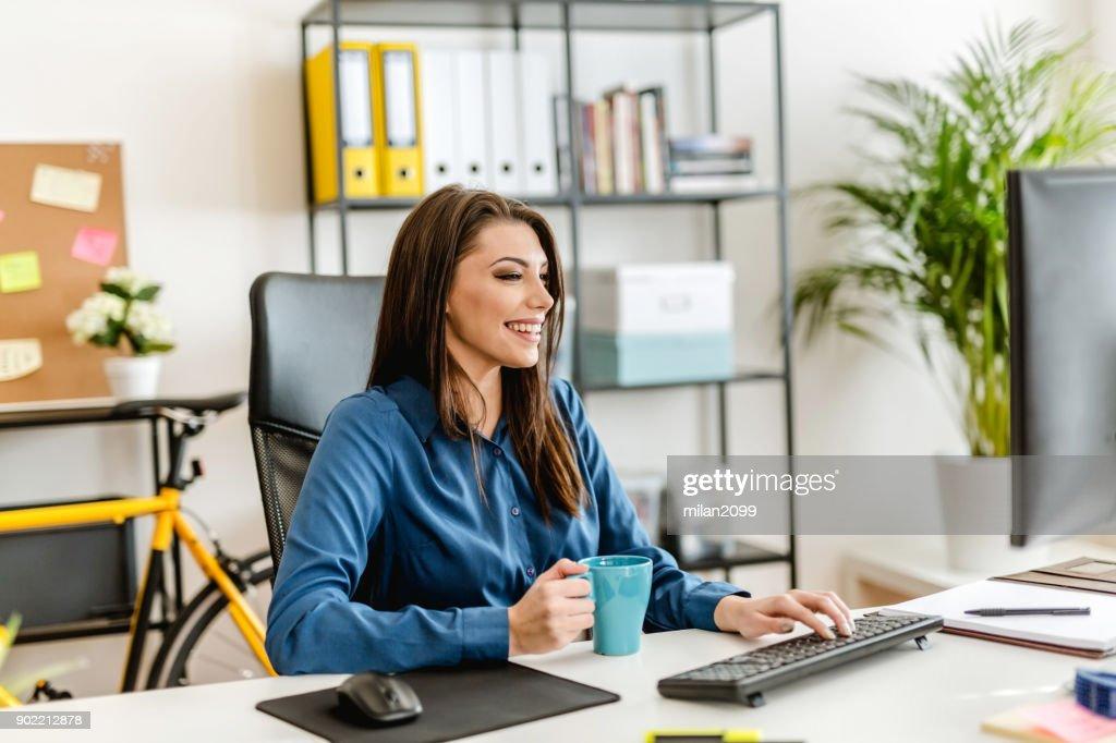 Junge Frau In Ihrem Buro Arbeiten Und Kaffee Trinken Stock Foto