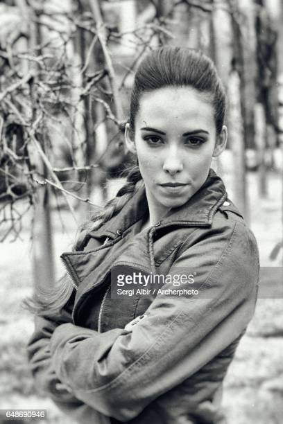 Young woman in her twenties, long hazel hair collected in a leather jacket (noisy picture).