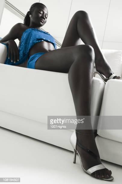 若い女性に高いヒールの高い白のソファー