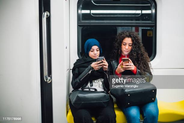 young woman in hijab and friend sitting on subway train looking at smartphones - zurückhaltende kleidung stock-fotos und bilder
