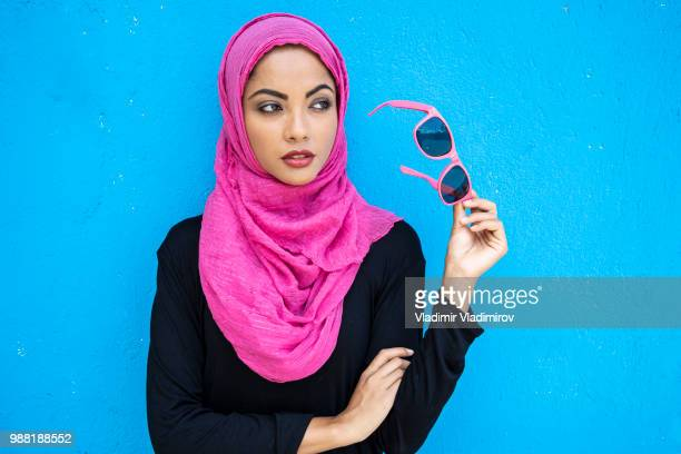 Young woman in hijab holding pink sunglasses