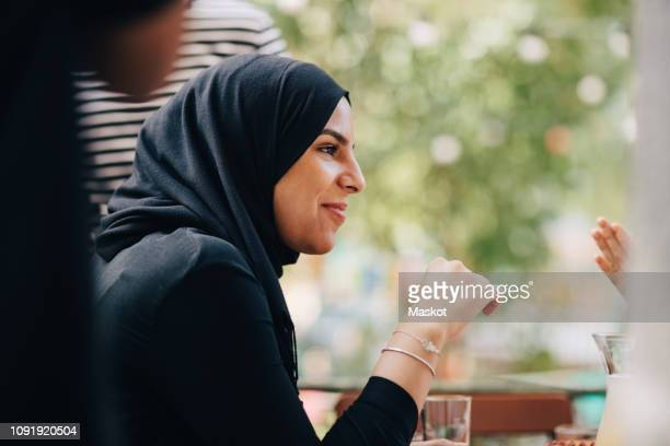 young woman in hijab looking away while sitting at balcony during party - hijab stock pictures, royalty-free photos & images