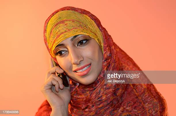 young woman in hijab speaking on mobile smiling - depczyk stock pictures, royalty-free photos & images