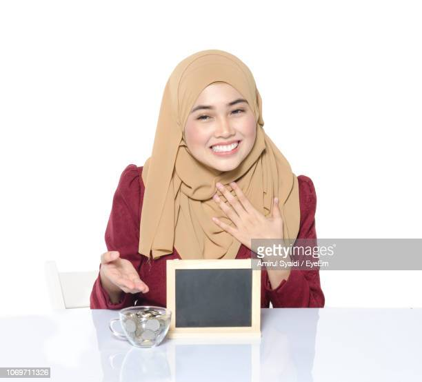 Young Woman In Hijab With Placard And Coins Against White Background