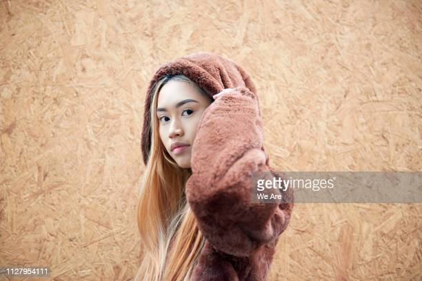 Young woman in hooded fur jacket.