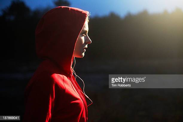 young woman in hooded top listening to music. - concentration stock pictures, royalty-free photos & images