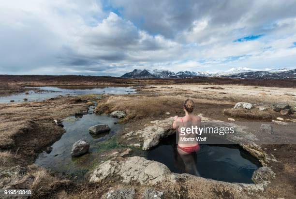 Young woman in hot spring looking towards mountains, Eyjar og Miklaholt, Western Region, Iceland