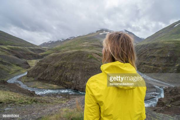 Young woman in Iceland contemplating canyon from top of it