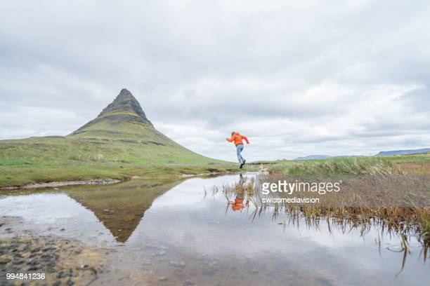 Young woman in Iceland jumping over fjord river at famous Kirkjufell mountain