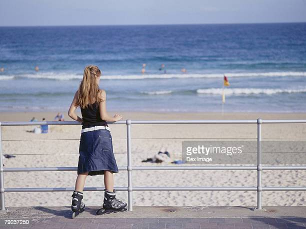 Young woman in inline skate leaning on railing, rear view