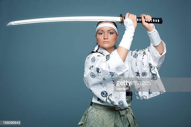 Young woman in japanese clothes defends herself with katana
