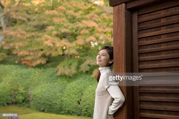 Young woman in Japanese garden, smiling