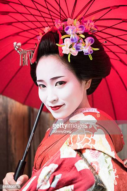 Young woman in Japanese geisha clothing with flowers in hair