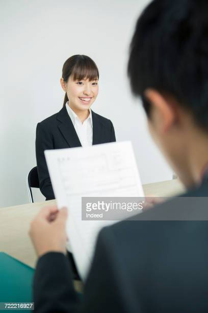 Young woman in job interview, businessman looking at her resume