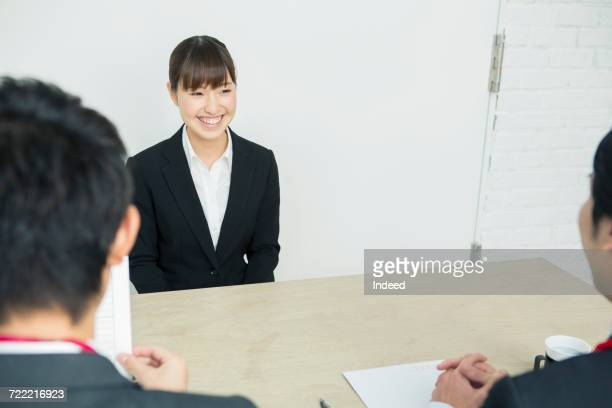 Young woman in job interview, facing to two businessmen