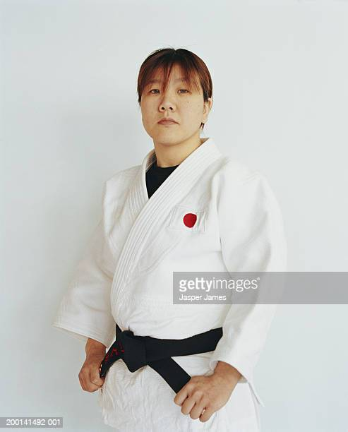 young woman in judo outfit, hands clasping belt, portrait - 柔道 ストックフォトと画像
