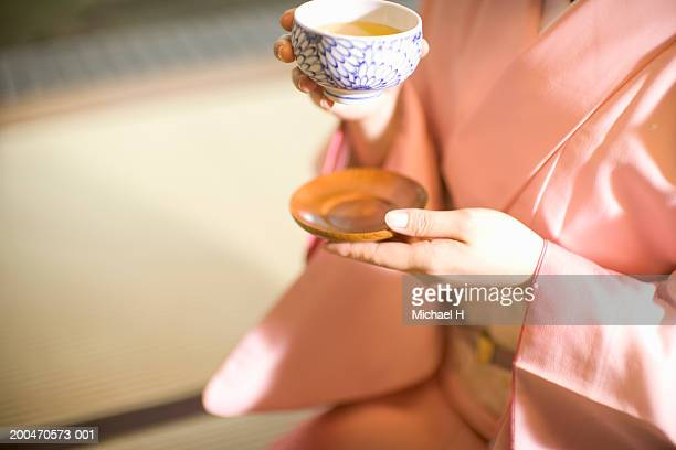 Young woman in kimono drinking green tea, mid section