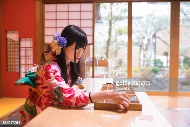 Jonge vrouw in Kimono ervaren bladgoud werkplaats plakken