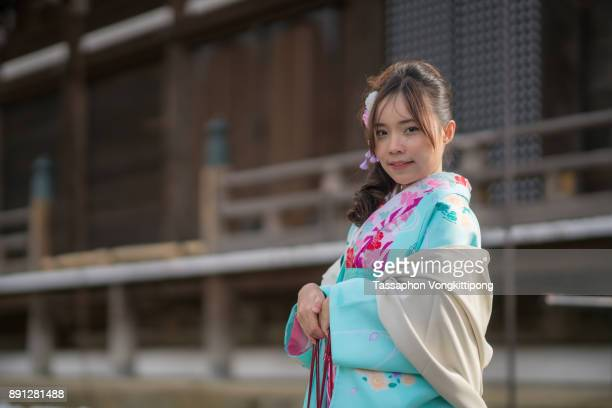 young woman in kimono front of japanese style building blurred background