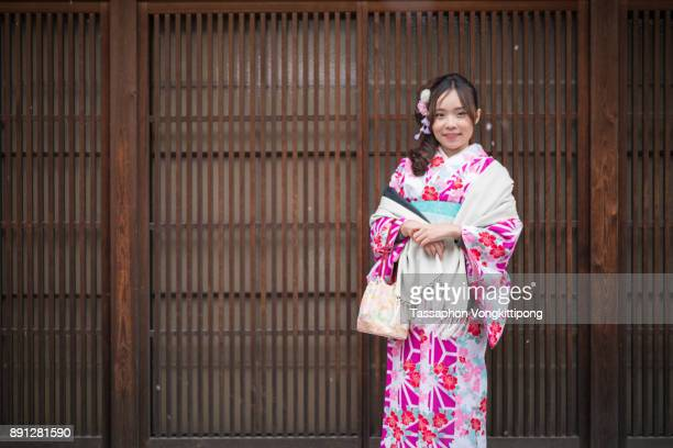 young woman in kimono front of pattern wooden wall