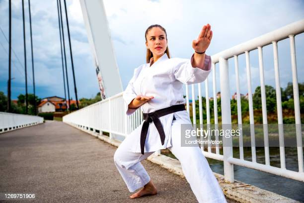 young woman in kimono practicing karate - martial arts stock pictures, royalty-free photos & images