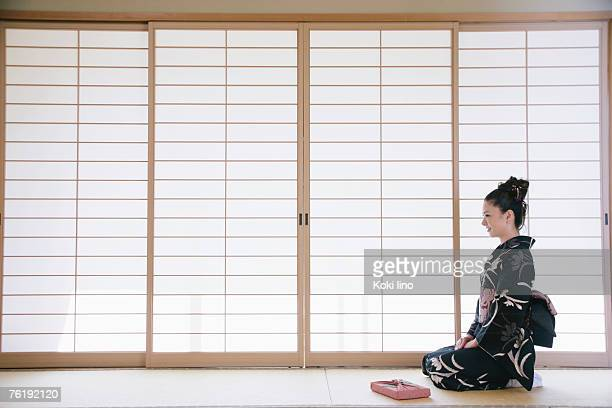 Young woman in kimono sitting on floor