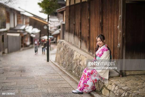 young woman in kimono sitting side of walkpath