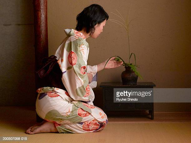 Young woman in kimono touching plant, side view
